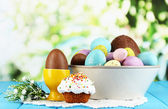 Composition of Easter and chocolate eggs on wooden table on natural background — Stock Photo