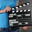 Movie production clapper board in hands on grey background — Stock Photo #22099423