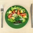 Fresh mixed salad with eggs, tomato, salad leaves and other vegetables on color plate, on wooden background - Stock Photo