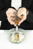Salvando, mãos femininas colocando moedas em frasco de vidro, isolado no branco — Foto Stock