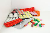 Colorful pills and capsules on shelf — Stock Photo