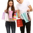 Young couple shopping and holding many shopping bags isolated on white — Stock Photo #22100305
