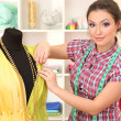 Stock Photo: Beautiful young dressmaker in workroom