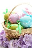 Světlé velikonoční vajíčka s luky v koši, izolované na bílém — Stock fotografie