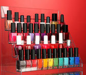 Bright nail polishes on shelf on red background — Stock Photo