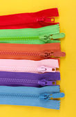 Multicolored zippers on yellow background — Stock Photo
