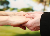 Priest holding woman hands, on green background — Stockfoto
