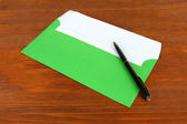 Envelope with pen on wooden background — Stock Photo