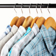 Shirts with ties on wooden hangers on light background — Stockfoto