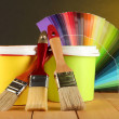 Paint pots, paintbrushes and coloured swatches on wooden table on dark yellow background — Foto de Stock