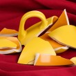 Yellow broken cup on table on fabric backgroun - Stock Photo