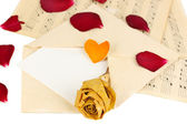 Old envelope with blank paper and dried rose on music sheets close up — Stock Photo