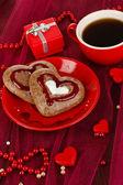 Biscuits au chocolat en forme de coeur avec une tasse de café le gros plan nappe rose — Photo