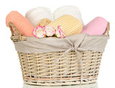 Bathroom towels folded in wicker basket isolated on white — Stock Photo