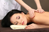 Beautiful young woman in spa salon getting massage, on dark background — Stock Photo