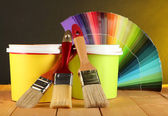 Paint pots, paintbrushes and coloured swatches on wooden table on dark yellow background — Stock Photo