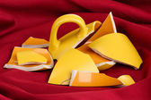 Yellow broken cup on table on fabric backgroun — Stock Photo