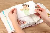 Foto's in handen en fotoalbum op houten tafel — Stockfoto