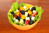 Tasty Greek salad on wooden background — Stock Photo