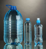 Different water bottles on grey background — Stock Photo