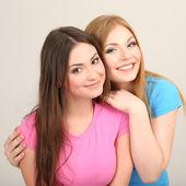 Dwie przyjaciółki przytulanie na szarym tle — Zdjęcie stockowe