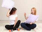 Dos amigas de almohadas en habitación — Foto de Stock