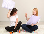 Two girl friends pillow fight on room — Foto Stock