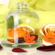 Decorative rose from dry orange peel in glass vase on green fabric background — Stock Photo