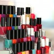Bright nail polishes on shelf in beauty salon - Stok fotoğraf