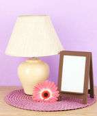 Brown photo frame and lamp on wooden table on lilac wall background — Stock Photo