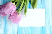 Krásnou kytici fialové tulipány a prázdné vizitky na modré dřevěné pozadí — Stock fotografie