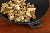 Gold pan with golden nuggets inside on wooden background — Stock Photo