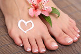 Beautiful woman legs with cream on bamboo mat — Stock Photo