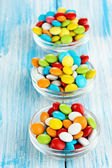 Colorful candies in glass bowls on blue wooden background — Stock Photo