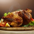 Whole roasted chicken with vegetables, on wooden table, on brown background — Stock Photo #22373823