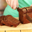 Woman slicing black bread on chopping board on wooden table close up — Stock Photo #22374489