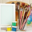 Photo frame as easel with artist's tools on wooden background — Stock Photo #22375155