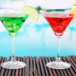 Glasses of cocktails on table near pool — Foto Stock