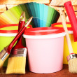 Set for painting: paint pots, brushes, paint-roller, palette of colors on stone wall background — Stock Photo #22376029