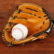 Stock Photo: Baseball glove and ball on wooden background
