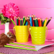 Royalty-Free Stock Photo: Colorful pencils in pails with copybooks and bear on table on pink background