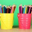 Colorful pencils in two pails on table on green background — Stock Photo #22376451