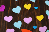 Many colorful paper hearts on wooden table close-up — Stock Photo