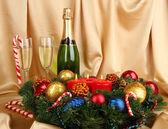 金の布の背景にシャンパンと組成の美しいクリスマスの花輪 — ストック写真