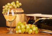 ワインの瓶、バレル、ワイングラス、茶色の背景に木製のテーブルでブドウの木製ケース — ストック写真