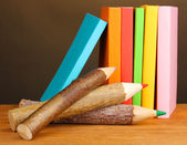 Colorful wooden pencils with books on wooden table on brown background — Stock Photo
