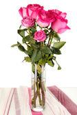 Krásné růžové růže ve váze na stole na bílém pozadí — Stock fotografie
