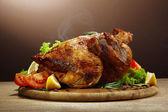 Whole roasted chicken with vegetables, on wooden table, on brown background — 图库照片