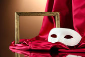 White mask, empty frame and golden silk fabric, on red background — Stock Photo