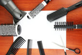 Comb brushes, hairdryer and cutting shears,on wooden background — Stock Photo